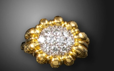 A diamond-set gold dress ring, c.1970, pavé-set with round brilliant-cut diamonds in a textured fluted gold mount, obscured mark to reverse (possibly French control mark) and rubbed maker's lozenge, size M