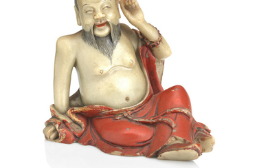 A gilt and lacquer decorated soapstone figure of a luohan