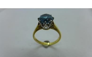 An 18ct gold and blue stone ring, possibly topaz, in a round...