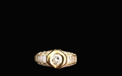 Ring in 18K (750°/°°) yellow gold set with a central brilliant-cut diamond surrounded by rows of baguette-cut diamonds between brilliant-cut diamonds.