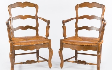 A PAIR OF FRENCH WALNUT LADDER BACK ELBOW CHAIRS WITH RUSHED SEATS ON STRETCHER BASES, 92CM H