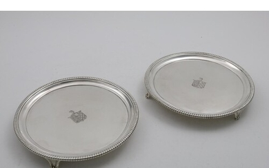 A PAIR OF GEORGE III CIRCULAR SALVERS with gadrooned borders...