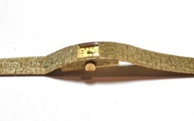 A lady's 9ct gold wristwatch, bark finished, integral bracelet with...