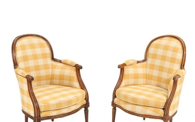 A pair of French 19th century walnut and stained beech Louis XVI style bergeres. (2)