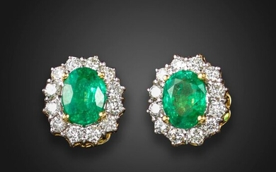A pair of emerald and diamond cluster earrings, each centred with an oval-shaped emerald within a surround of round brilliant-cut diamonds in gold, post fittings, 1.2cm high