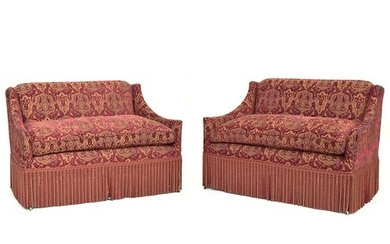 A pair of modern upholstered banquettes with fringe, on faux...
