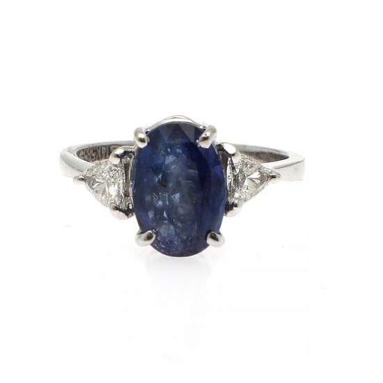 NOT SOLD. A sapphire and diamond ring set with an oval-cut sapphire flanked by two...