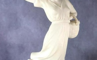 Carved Alabaster Figure of a Young Woman, a 1920's era girl in a wind blown dress carrying a basket of flowers. 18.5 in.h. Condition: Very good with some minor chips.