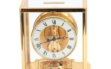 "Jaeger-LeCoultre: ""Atmos"". Brass and glass table clock, circular white enamel chapter ring. 20th century. H. 23. W. 20. D. 15 cm."