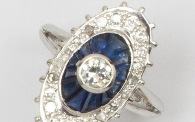 Oval ring in white gold, set with a brilliant-cut diamond in a double surround of calibrated sapphires and smaller diamonds. Finger size: 52. P. Brut: 7.3g.