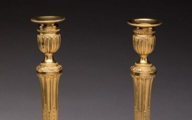 Pair of LOUIS XVI FLAMBEAUX in chased and gilt bronze. The shaft with rough grooves with asparagus tips, on a base with a laurel cord and a frieze of pearls. The vase style holders on pedestals with friezes of pearls. Original bobèches. Gilding with...