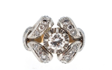 Ring in 18 K yellow gold (750 °/°°°) and platinum (950 °/°°) set with a brilliant cut diamond of about 0.50 ct in the centre, in a setting of volutes paved with small brilliants.