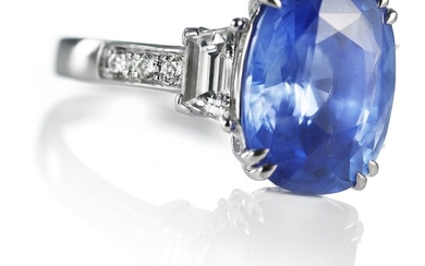 WIN: A Ceylon sapphire and diamond ring set with a natural Cornflower Blue Ceylon sapphire weighing app. 8.05 ct. flanked by diamonds, mounted in 18k white gold