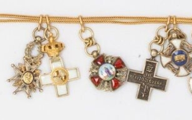 Yellow gold pin and chain holding various yellow gold reductions and argent : seven enamelled decorations, two medals and two war crosses. P. Brut : 17.9g.