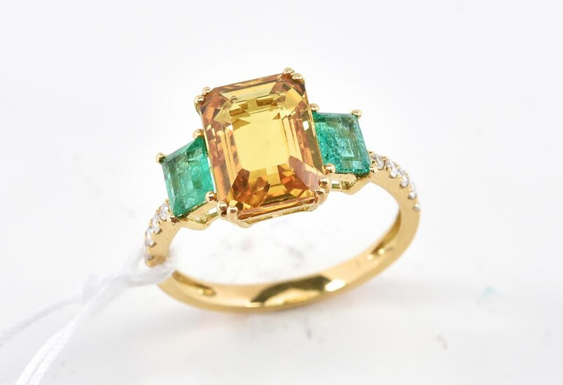 A SAPPHIRE, DIAMOND AND EMERALD RING - Featuring a yellow emerald cut sapphire weighing 3.83cts, shouldered by two rectangular emera...