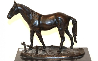 A bronze model of a horse on a black marble...