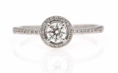 A diamond ring set with a brilliant-cut diamond weighing app. 0.30 ct. encircled by numerous...