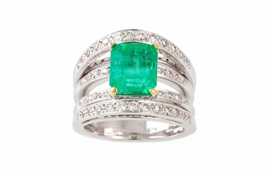 AN EMERALD AND DIAMOND DRESS RING, the trap cut emerald to a...