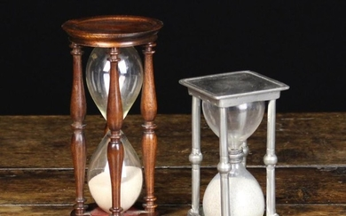 An Antique Pewter Egg Timer; the glass twin-chamber between a square top & base ornamented with wrig