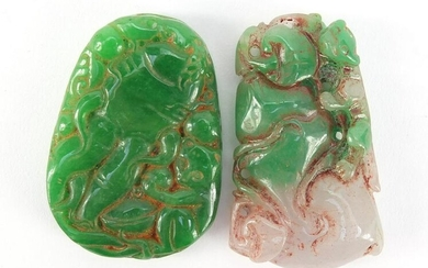 Two Chinese carved green jade pendants, the largest