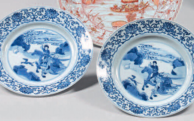 Two china plates. Kangxi (1662-1722), six-character mark, Chenghua, in blue under cover in a double circle. With blue-white decoration, in the center of riders hunting in a landscape in a medallion with circles, the wing of arabesques with lotus...