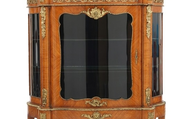 A Napoleon III fruitwood (?) display cabinet with gilt-bronze mountings and ornaments. Two glass shelves. France, ca. 1870. H. 135 cm. W. 122 cm. D. 47 cm.