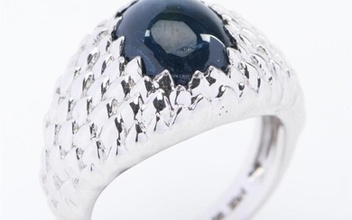 A STAR SAPPHIRE SIGNET RING IN 18CT WHITE GOLD, FEATURING CABOCHON CUT BLUE SAPPHIRE WEIGHING 4CTS, WITHIN A TEXTURED DOMED SURROUND...