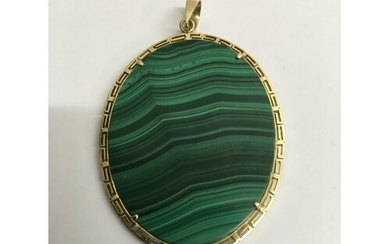 A oval malachite pendant surrounded with a 14 k gold mount ....