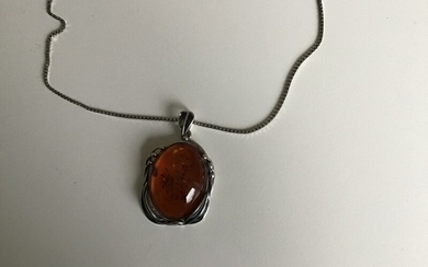 An amber necklace with pendant set with cabochon-cut amber, mounted in sterling silver. Necklace L. 42 cm. Pendant H. 4.8 cm. W. 3 cm.