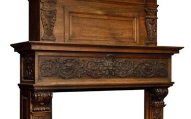Monumental walnut mantel carved in the neo-Renaissance taste of rinceaux, dolphins and masks. Second half of the 19th century. H: 250 cm, W: 192 cm, D: 55 cm