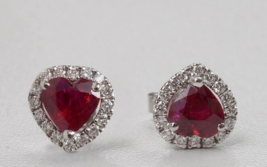 """Pair of 18 karat white gold earrings set with two heart cut rubies for a total of +/-1.54 carats (colour: """"pigeon's blood"""") and brilliant-cut diamonds for a total of +/-0.28 carat (Colour: E-F; Purity VS). Size: +/-0.9x0.9cm. Total weight: +/-1.9 gr."""