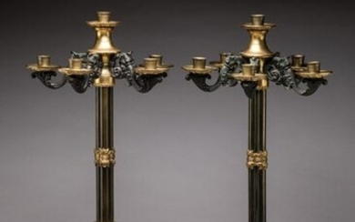 Pair of TORCHERS with five light arms and a bronze top light alternating gilt bronze and gunmetal patina bronze. The arms of light with foliated windings radiating around a spinning top each receive bobèches with scroll decoration. It rests on a...