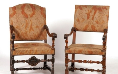 Two walnut armchairs carved with acanthus leaves. One decorated with a shell with figures. 17th century. H.105 W.64,5 D.75,5 cm and H.104,5 W.58 D.56 cm. Restorations of use.