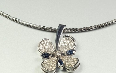18K (750/oo) white gold pendant featuring a four-leaf clover centered on a brilliant cut diamond, the petals paved with diamonds and adorned with three shuttle sapphires. It is held in place by its flat palm-tree link white gold chain (the clasp is in...