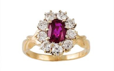 A RUBY AND DIAMOND CLUSTER RING, the oval ruby to a brillian...