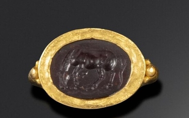 A Roman garnet intaglio depicting a horse, c1st century BC - 1st century AD, the horse grazing and stamping its hoof, in a gold ring mount probably c3rd - 4th century AD Mesopotamian, intaglio 1.4cm wide, ring size N approximately