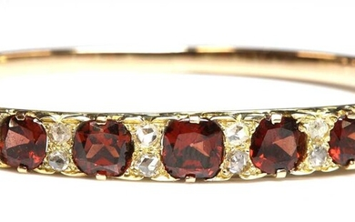A gold garnet and diamond carved head-style hinged bangle