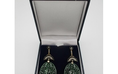 A pair of Asian 9ct gold and silver drop earrings, the carve...