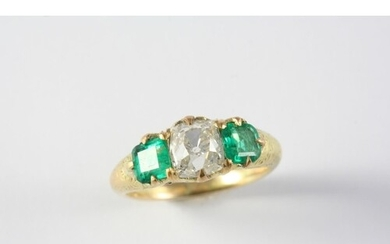 AN EMERALD AND DIAMOND THREE STONE RING the cushion-shaped d...