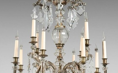 Chandelier with four bunches of three branches of lights in gilded metal dressed in glass. It is decorated with cut crystal plates.