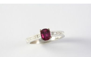 A RUBY AND DIAMOND RING the oval-shaped ruby is set with fiv...