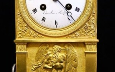 A gilt bronze and chiselled clock with a bas-relief of Cronos on an amati background framed by two pilasters with pediments.