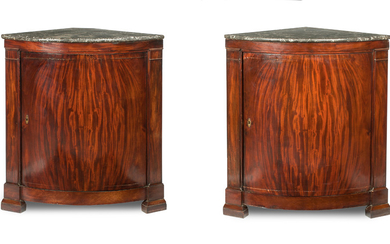 A pair of early 19th century German figured mahogany bowfronted marble top corner cabinets