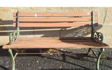 A slatted wood garden bench with metal supports and a white...