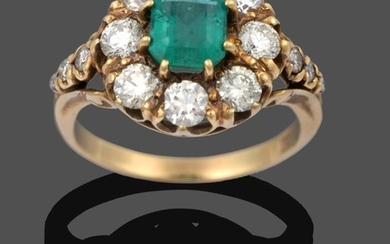 An Emerald and Diamond Cluster Ring, the emerald-cut emerald within...