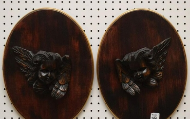 Pair Carved Angel Heads mounted on oval mahogany