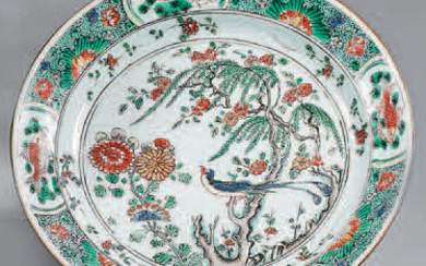 Small porcelain dish. Kangxi (1662-1722). Decorated with Green Family enamels, in the centre of a large tree with a bird and flowering rocks in a circled medallion, flowers thrown on the waterfall, the wing with fish and shrimps in interposed...