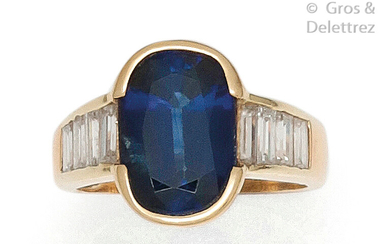Yellow gold ring set with an oval faceted sapphire set with baguette diamonds. Tour of doigt : 53. P. Brut : 6.6 g.