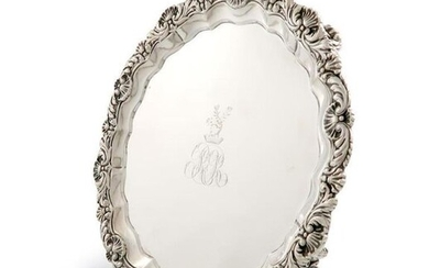 A George III silver salver, by Philip Rundell, London 1819, of circular form, foliate and shell border, the centre with initials below a crest, on four trailing grapevine scroll bracket feet, diameter 22.5cm, approx. weight 19.3oz. The crest is that of...