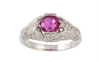 A RUBY AND DIAMOND DRESS RING, the oval ruby to a pavé set d...